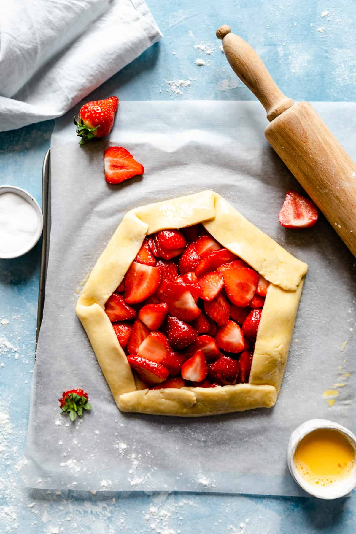 top view of unbaked strawberry galette on a blue background