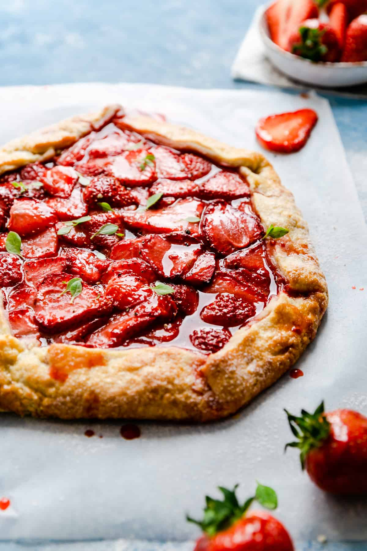 angle shot of strawberry galette with some basil leaves on top