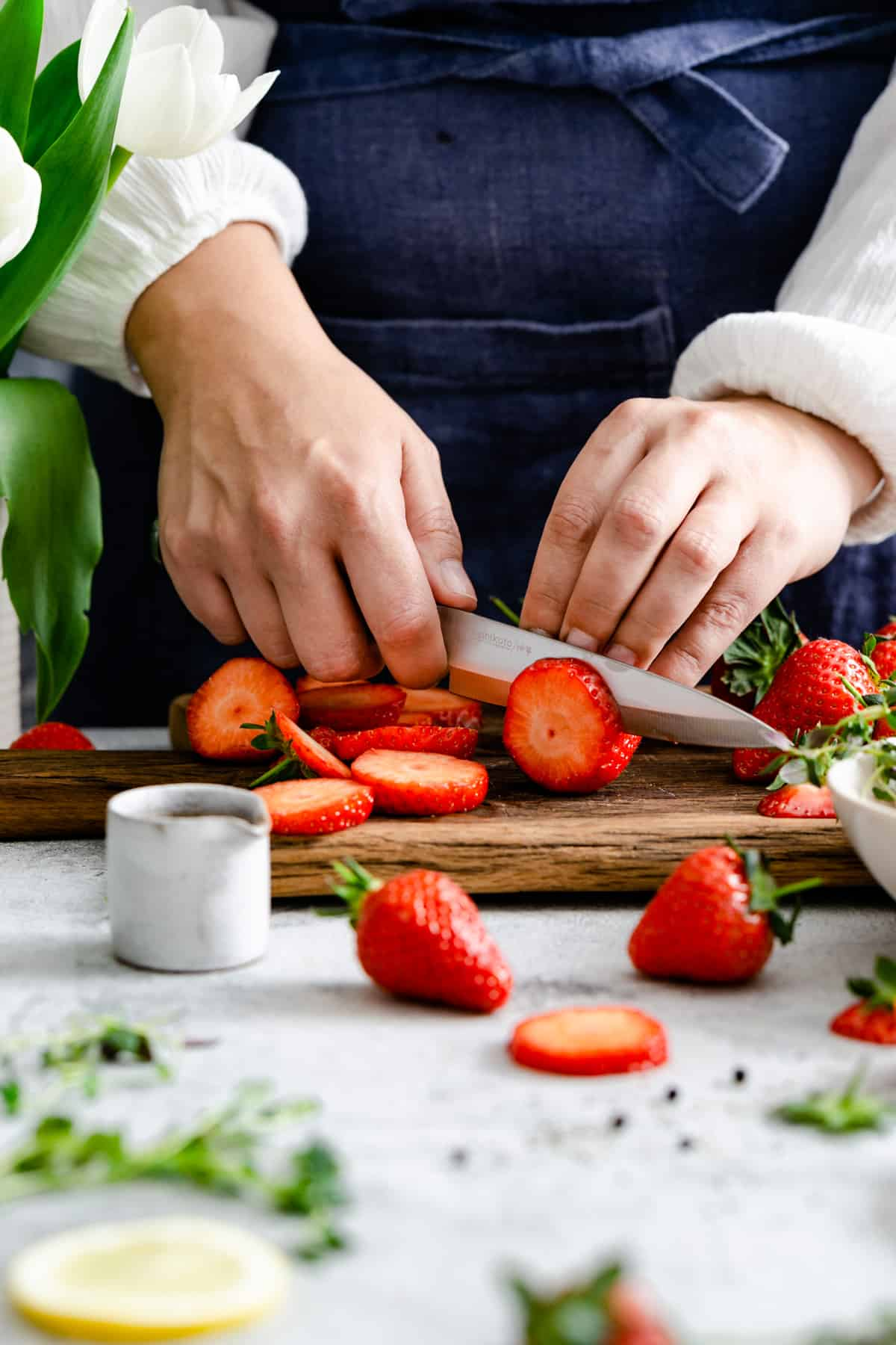 a close up of a person's hands slicing strawberries on a wooden chopping board