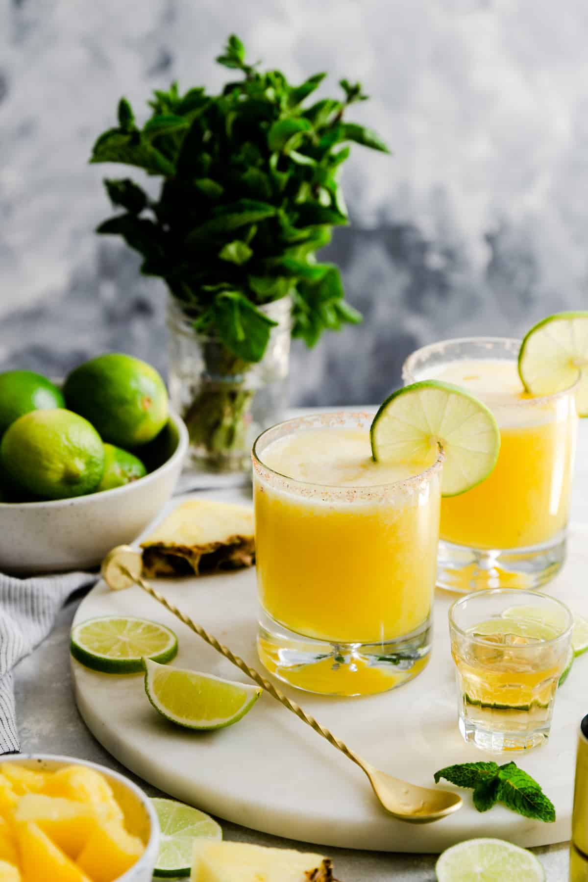 two glasses with pineapple margaritas on a marble chopping board