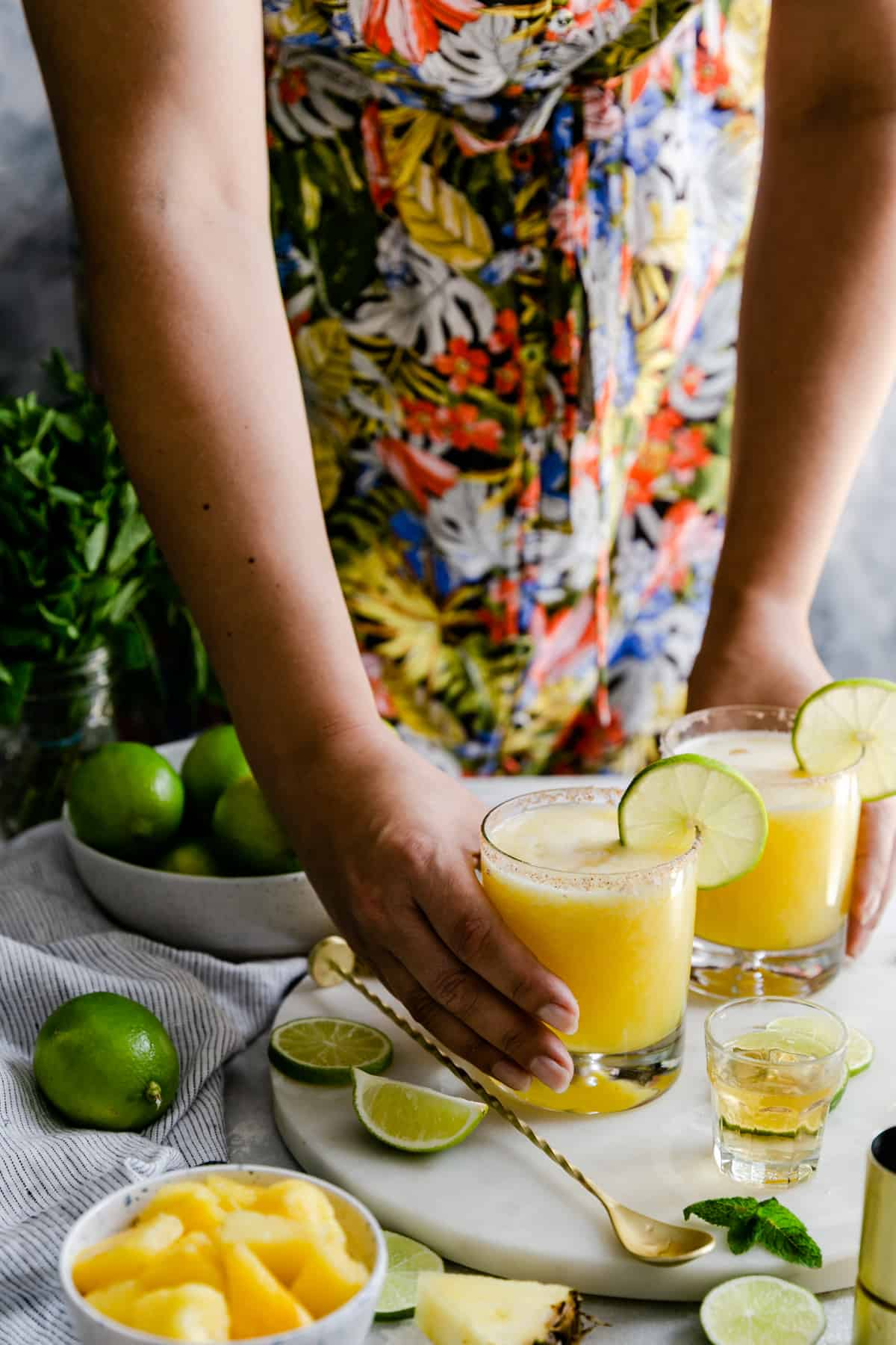 a person holding two glasses of frozen pineapple margaritas