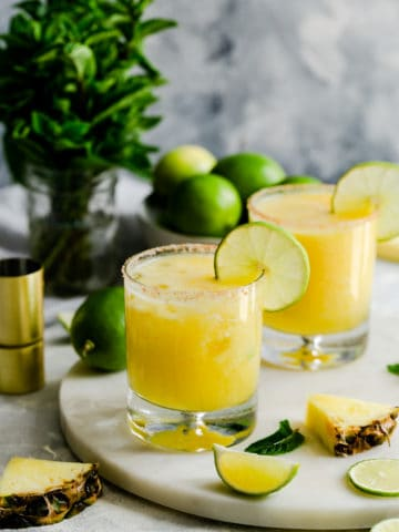 two glasses filled with pineapple margarita cocktail