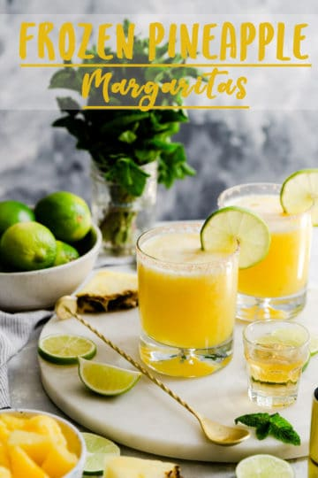 two glasses with frozen pineapple margaritas on a white marble board