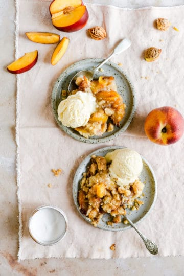 two small plates with peach cobbler topped with vanilla ice cream