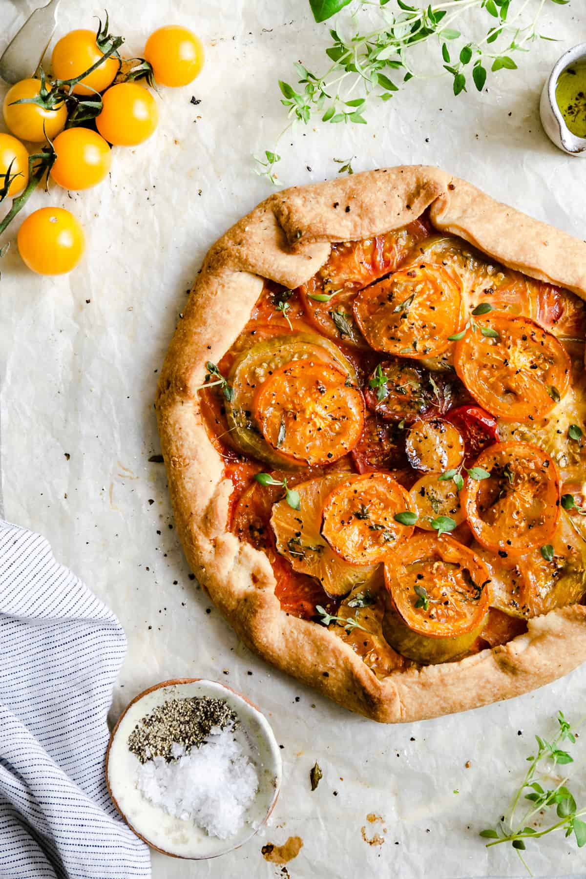 overhead shot of summer tomato galette topped with fresh thyme and black pepper