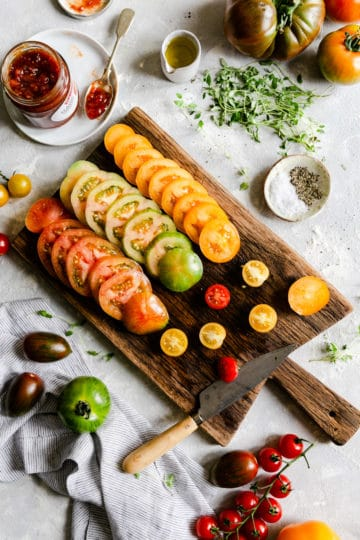top view of sliced tomatoes on a wooden chopping board