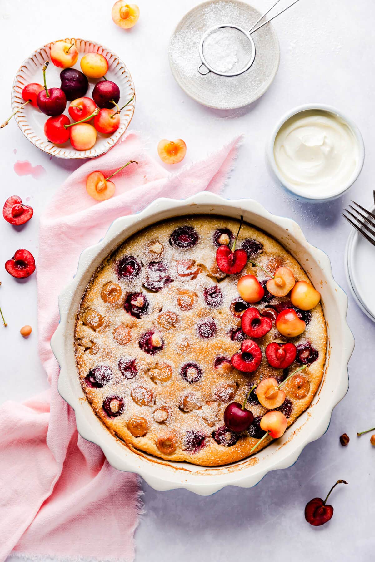 Cherry clafoutis in a baking dish with some fresh cherries on side