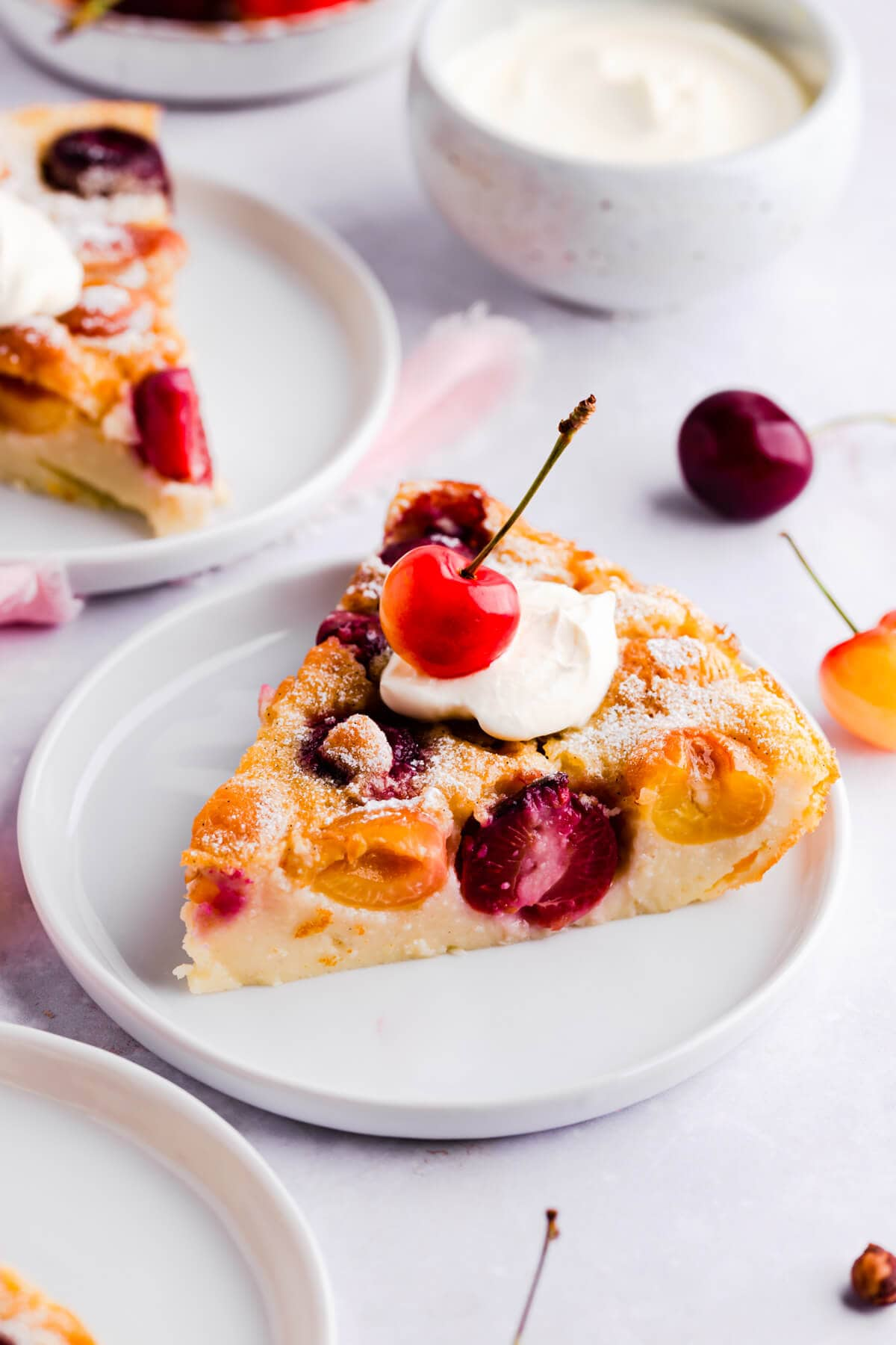 close up of a slice of cherry clafoutis on a small plate