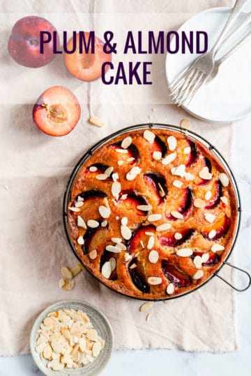 top view of a cake topped with plums and almonds
