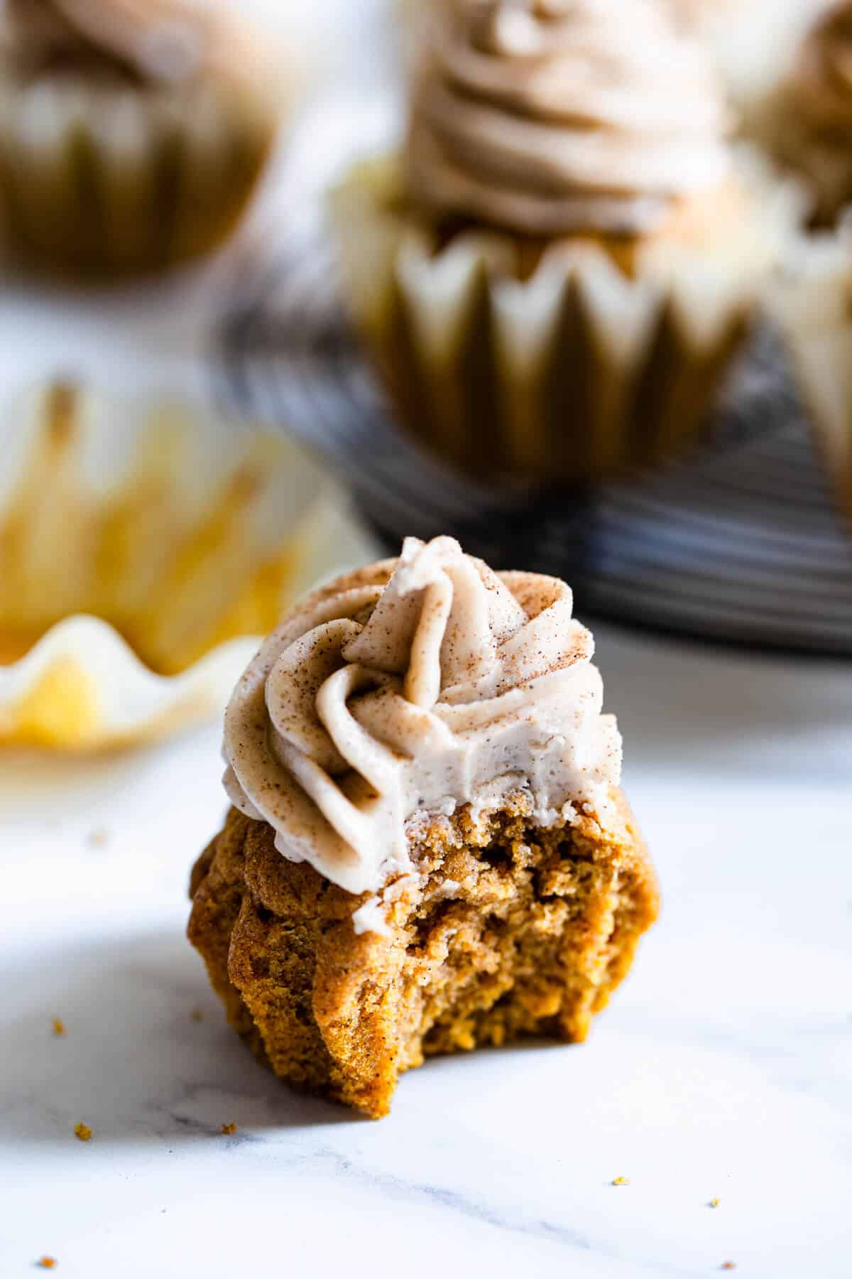 close up of a pumpkin cupcake with bite taken out of it