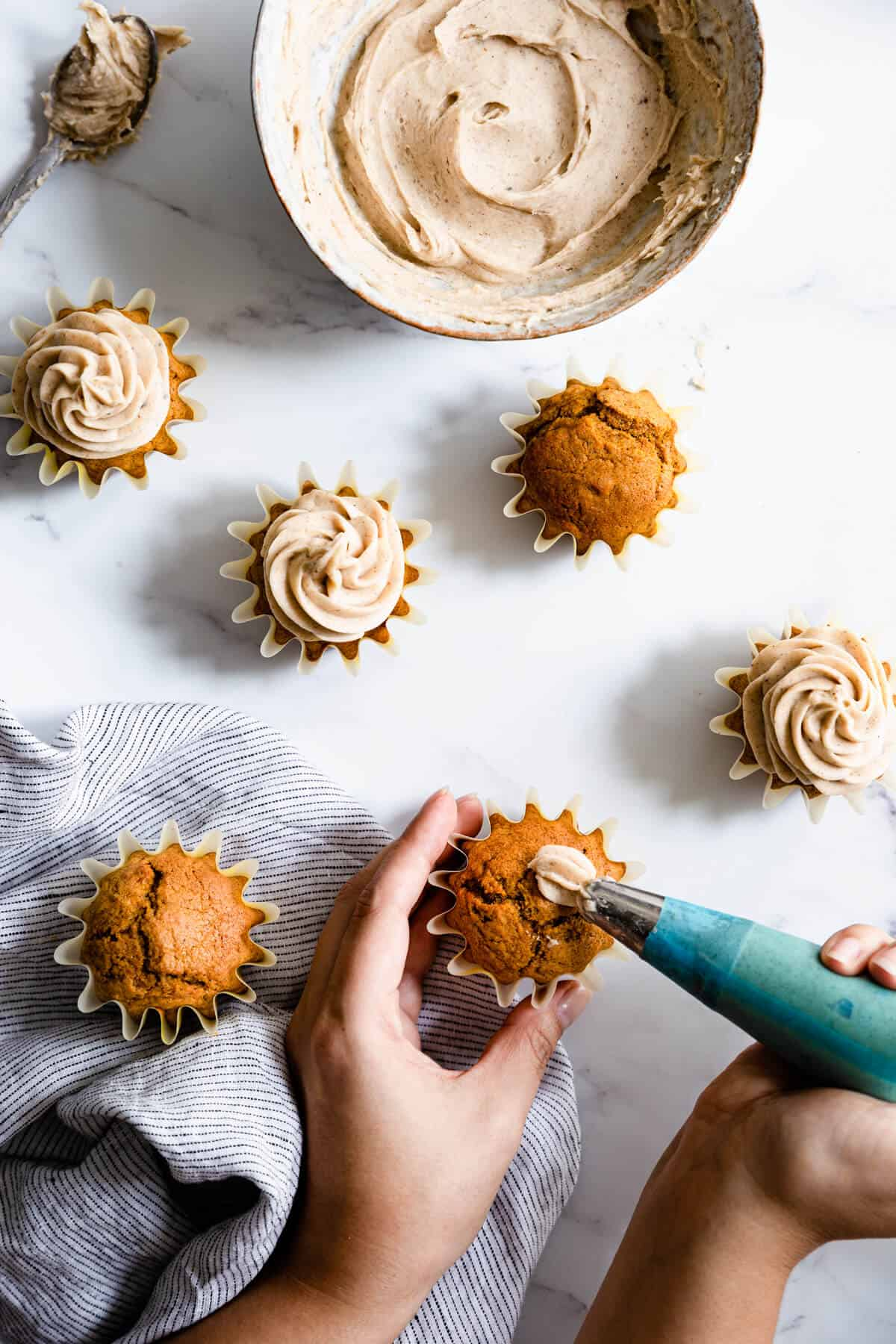 a person piping chai frosting on top of pumpkin cupcakes