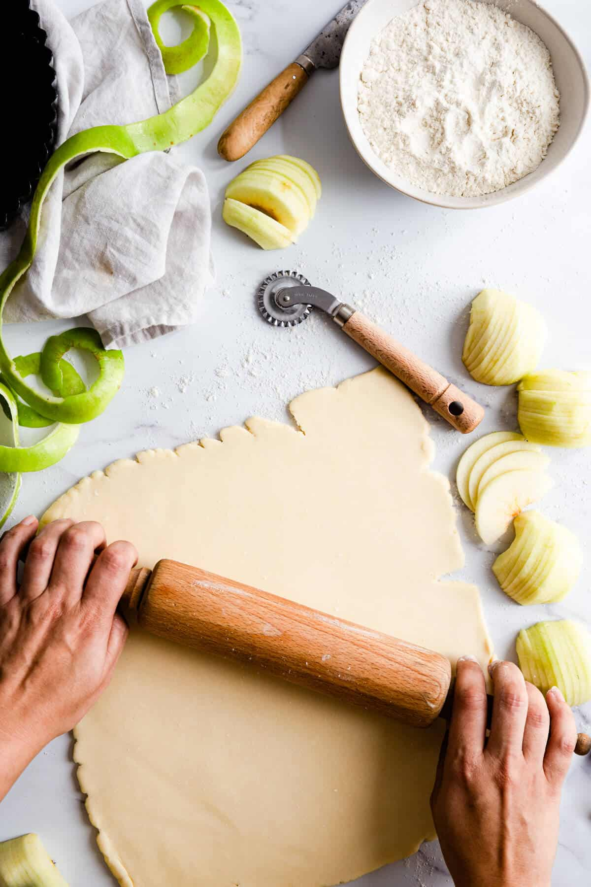 top view of a person rolling some pastry with a rolling pin