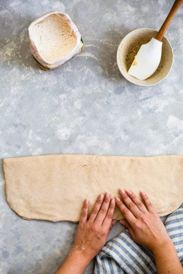 overhead shot of a person folding the dough for cardamom buns