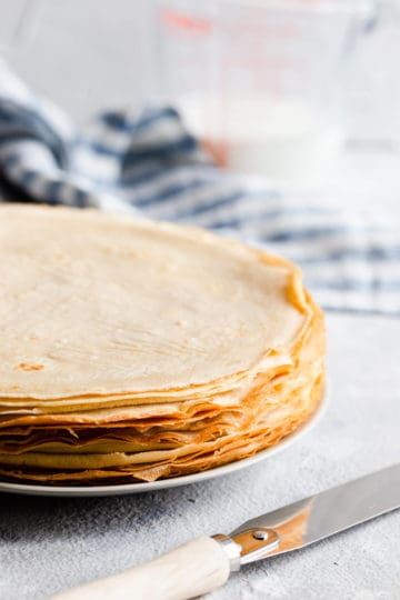 side close up of a stack of golden crepes
