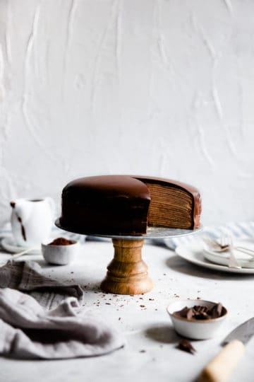 side shot of crepe cake on a cake stand with a slice cut out