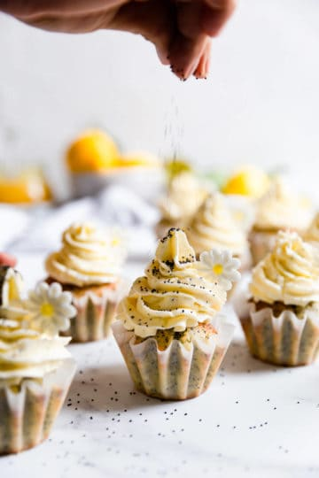 side view of poppyseeds being sprinkled onto the cupcake