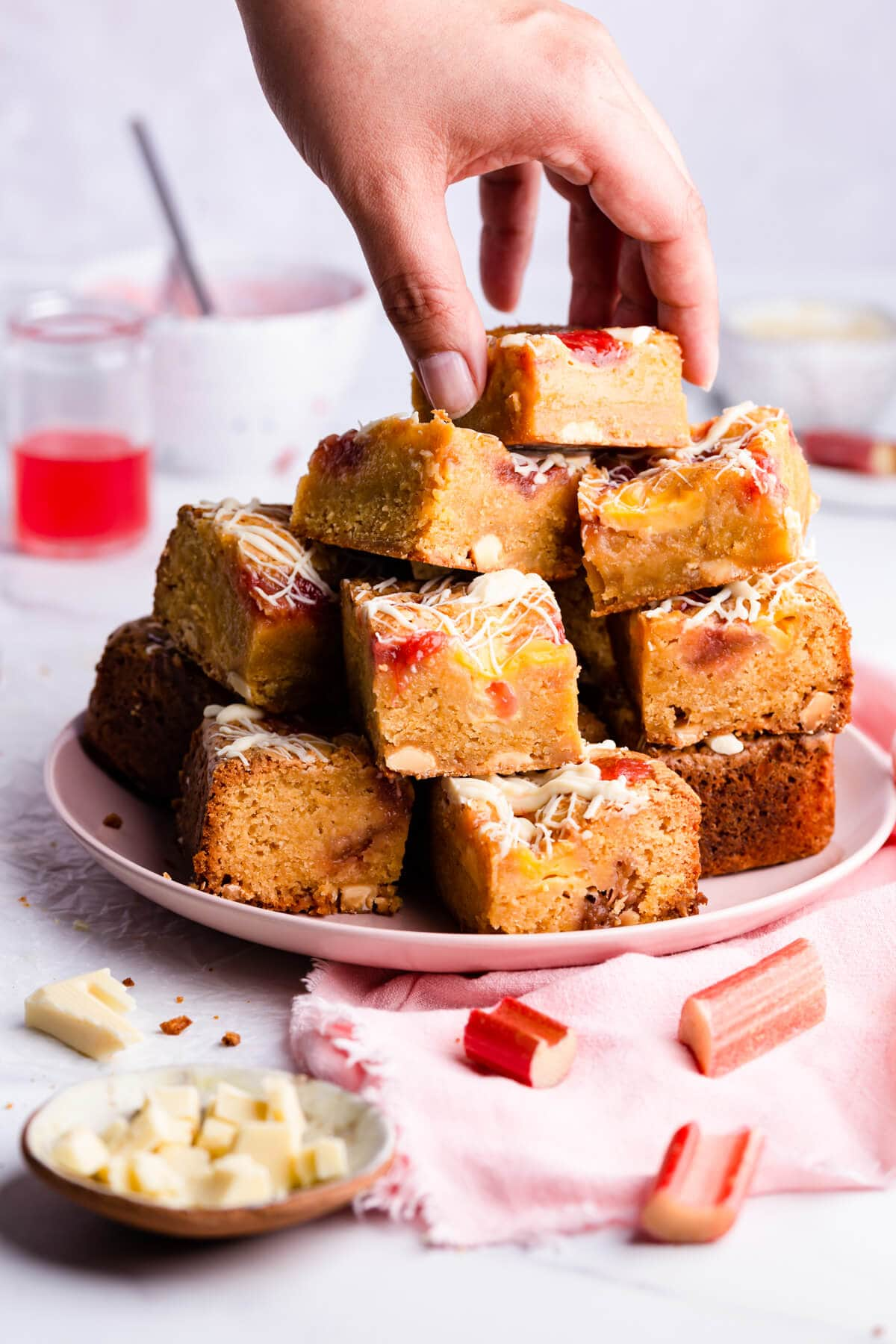 side close up at a plate filled with blondies cake squares and a person taking a piece from the top