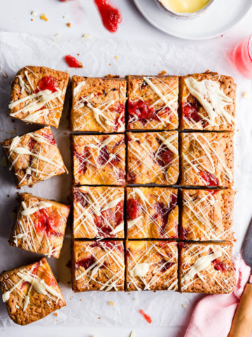 top view of square slices of blondies topped with rhubarb and custard