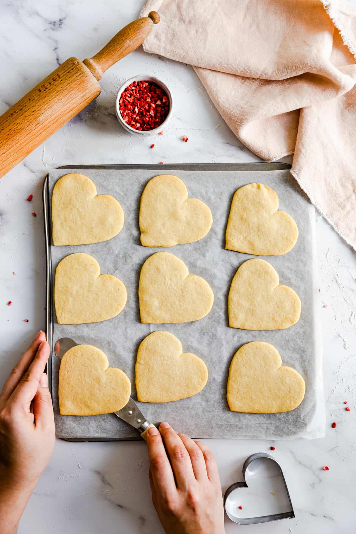 top view of a person removing a sugar cookie from baking tray