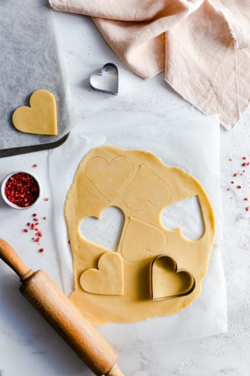 overhead shot of rolled out cookie dough with hearts cut out of it