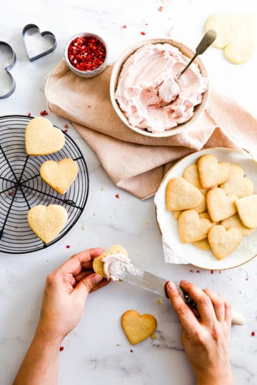 overhead view of a person spreading whipped cream on sugar cookies