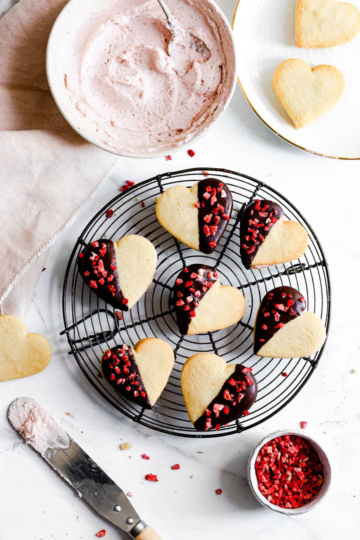 top view of sugar cookies dipped in chocolate and sprinkled with dried strawberries