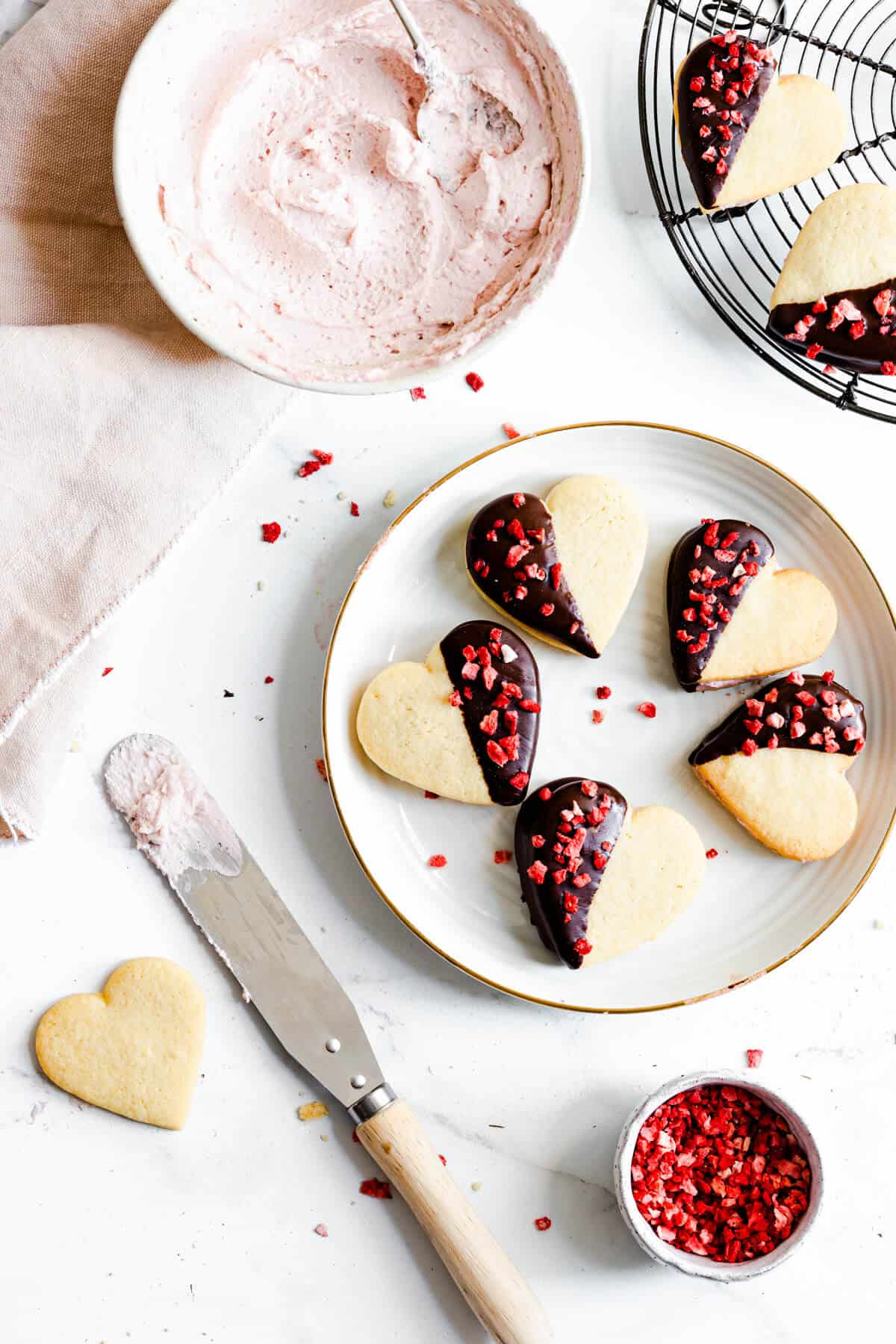 overhead view of five heart sandwich cookies on a plate