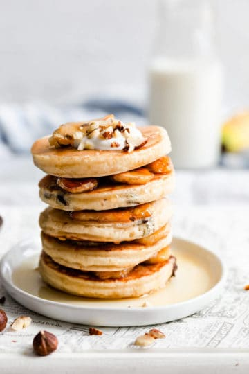 side close up of a stack of pancakes with caramelised bananas between them