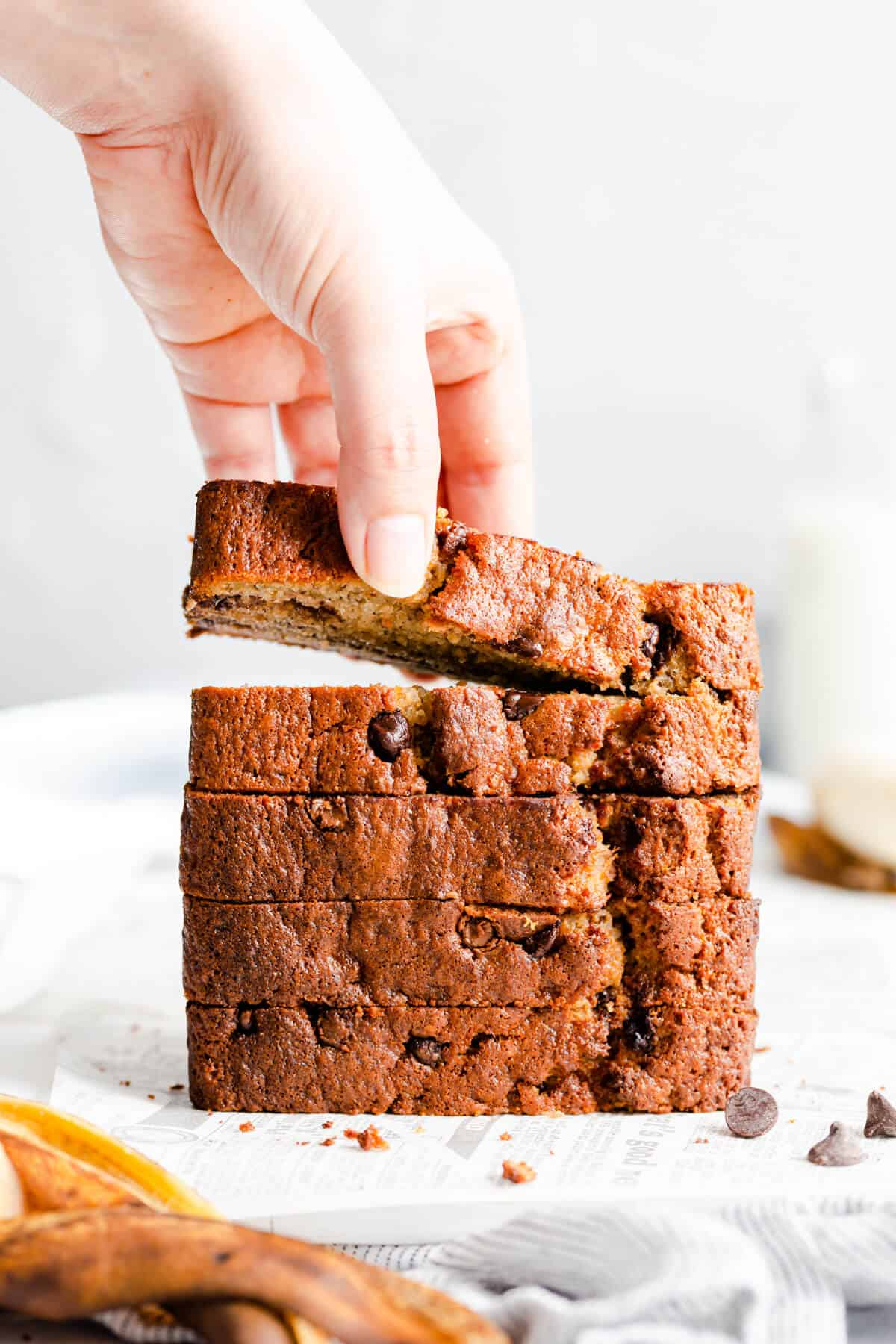 straight-ahead shot of a person taking a slice of banana bread from a stack of slices