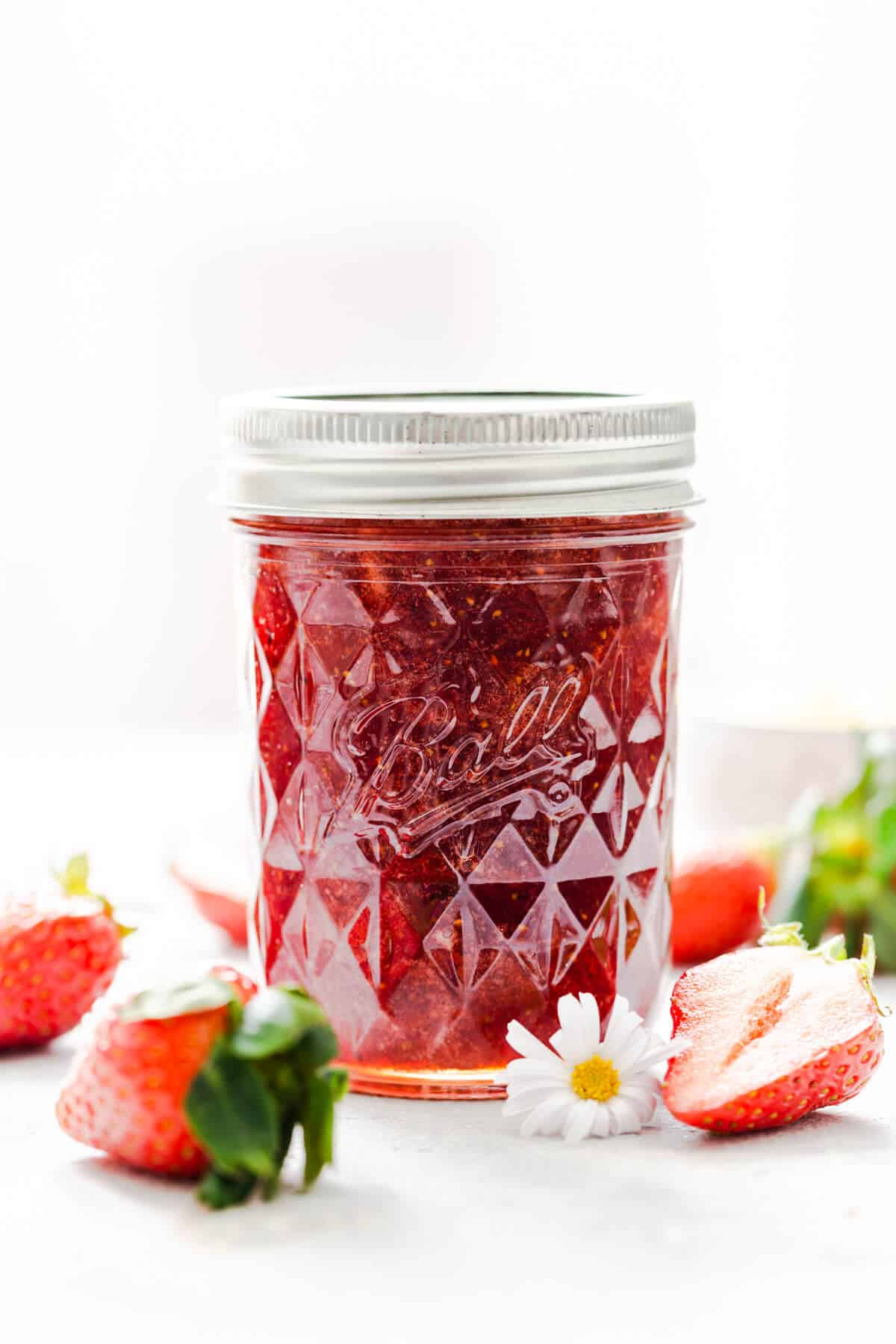 straight ahead shot at a jar with strawberry jam and some strawberries around it