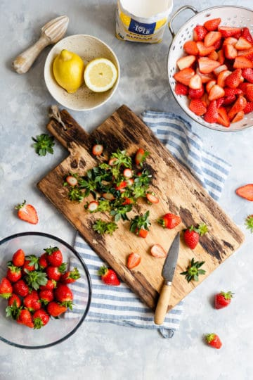 overhead shot of strawberries on a wooden chopping board
