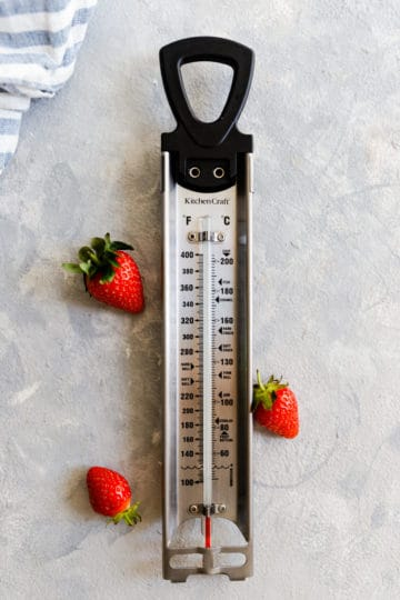 top view of a kitchen thermometer with few strawberries next to it