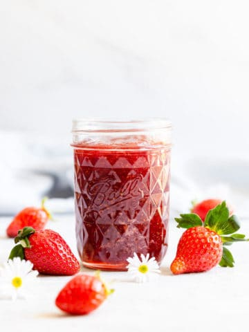 straight ahead angle shot of a jar with strawberry jam and fresh strawberries on side