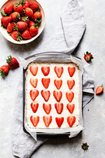 overhead shot of baking tin with coconut strawberry ice topped with strawberries