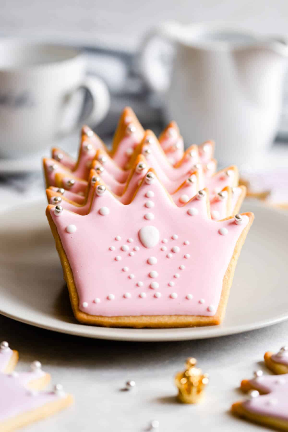 side close up shot of crown shaped sugar cookies with pink icing