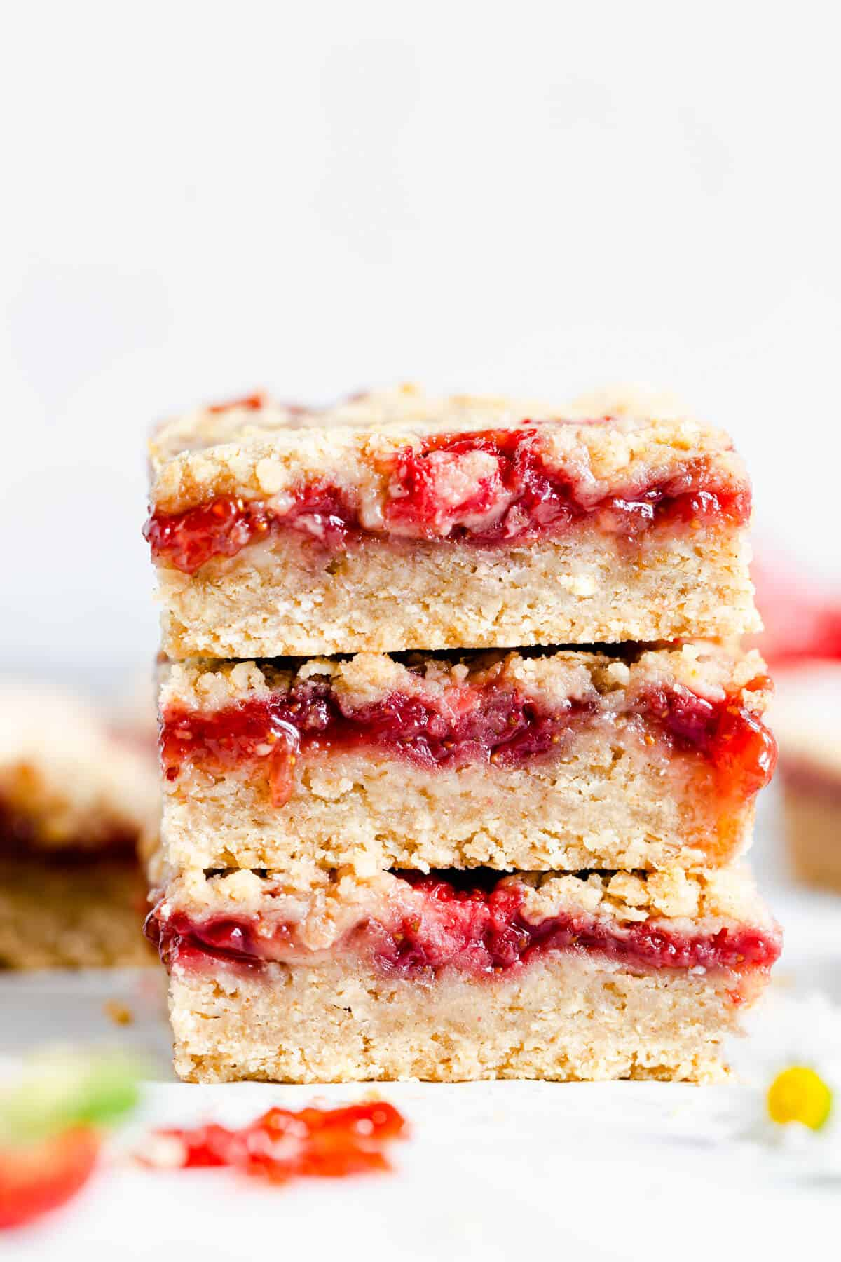 straight ahead close up shot of 3 strawberry crumble bars stacked on top of each other