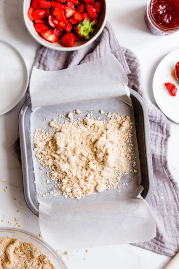 overhead shot of a baking tin with paper and crumble inside