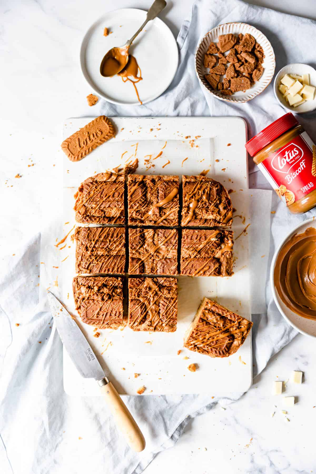 top view of blondies cut into square slices with some biscoff biscuits and biscoff spread on side