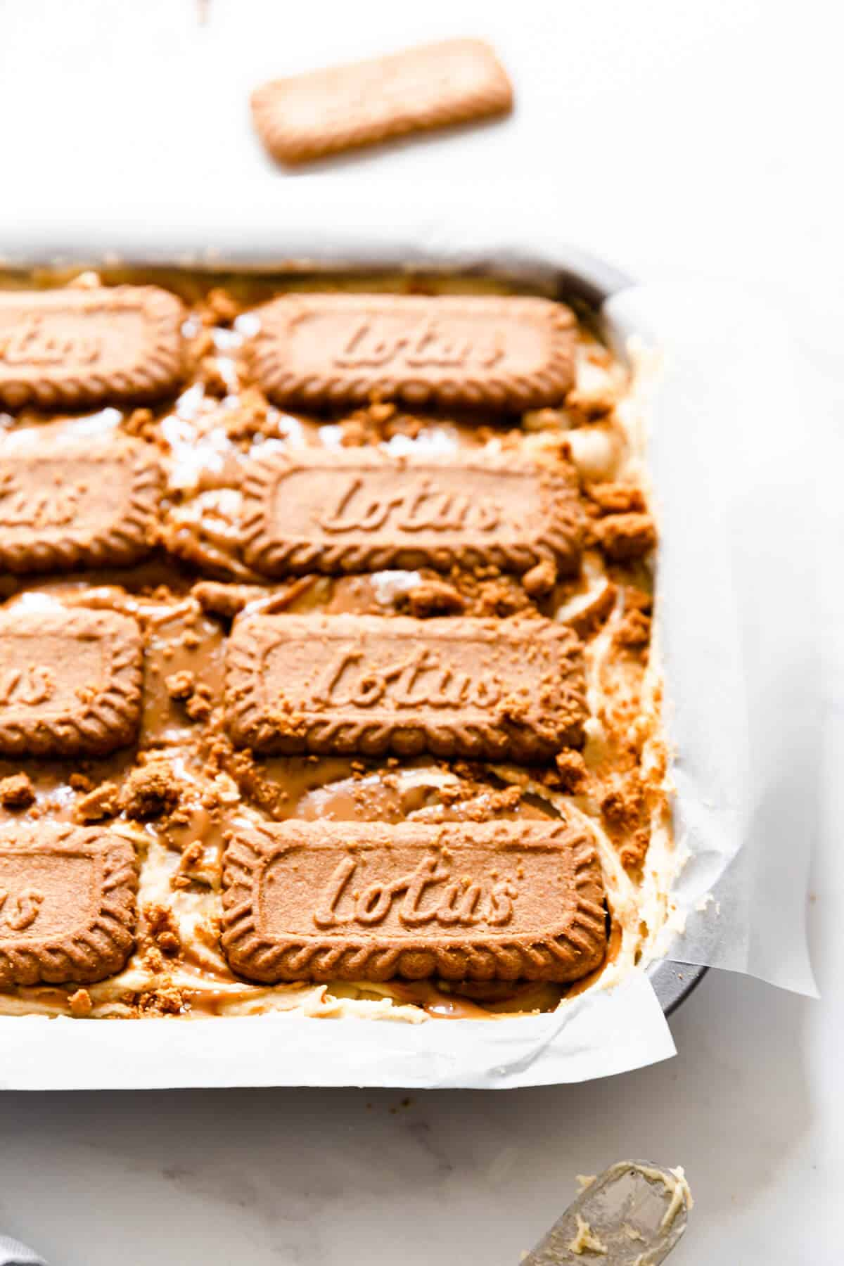 side close up of a baking tin with cake batter topped with biscoff biscuits