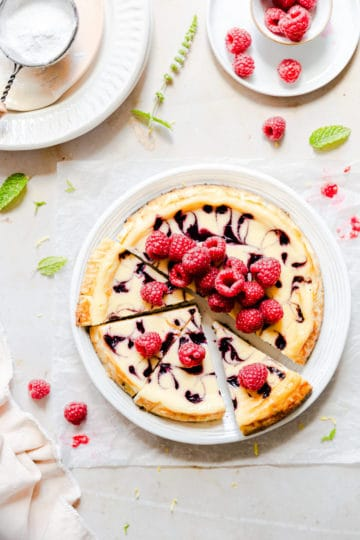 top view of a cheesecake topped with fresh raspberries and raspberry sauce