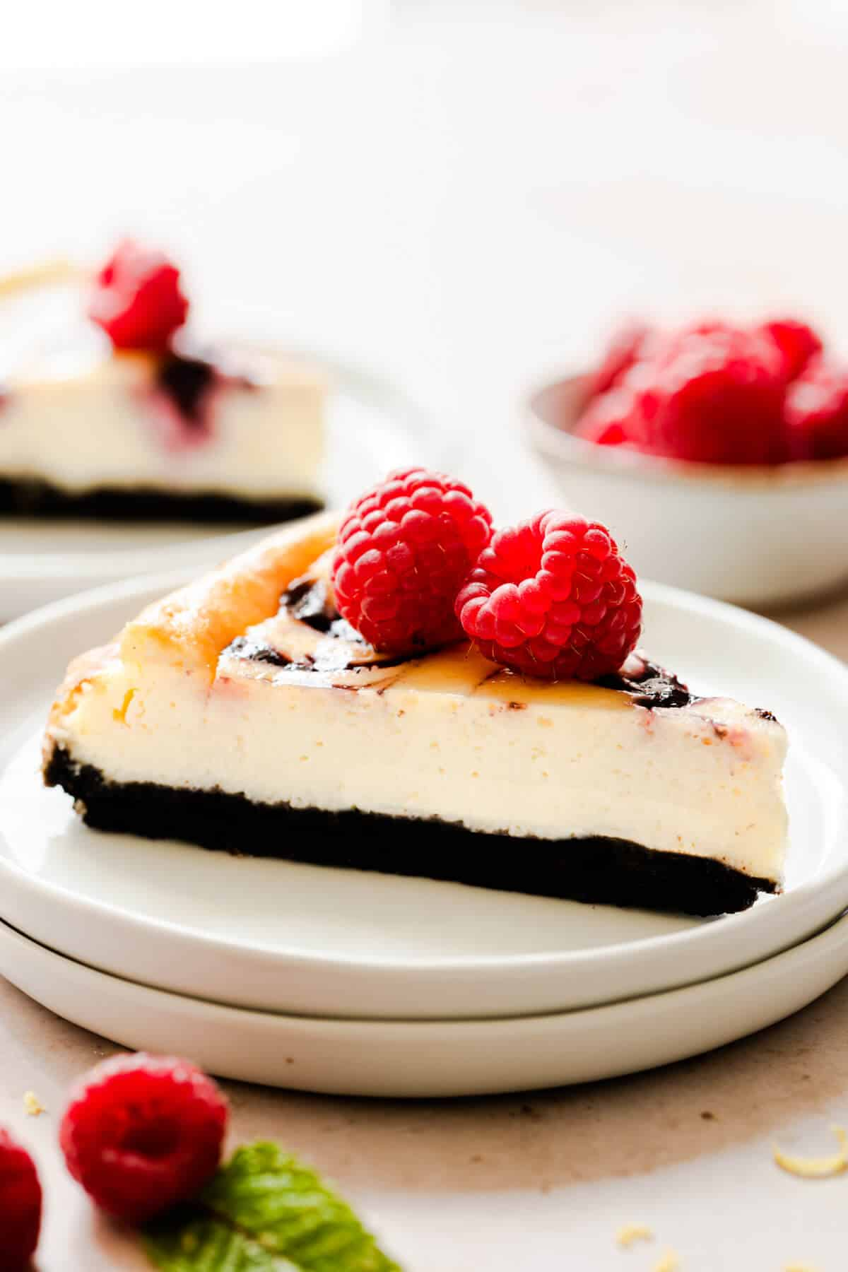 side close up at a slice of raspberry ripple cheesecake on a small plate