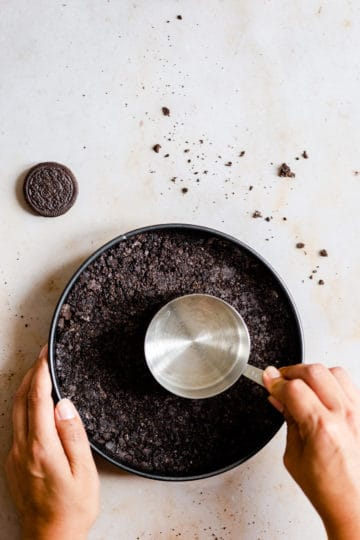 top view of person pressing oreo crust into bottom of baking tin with measuring cup