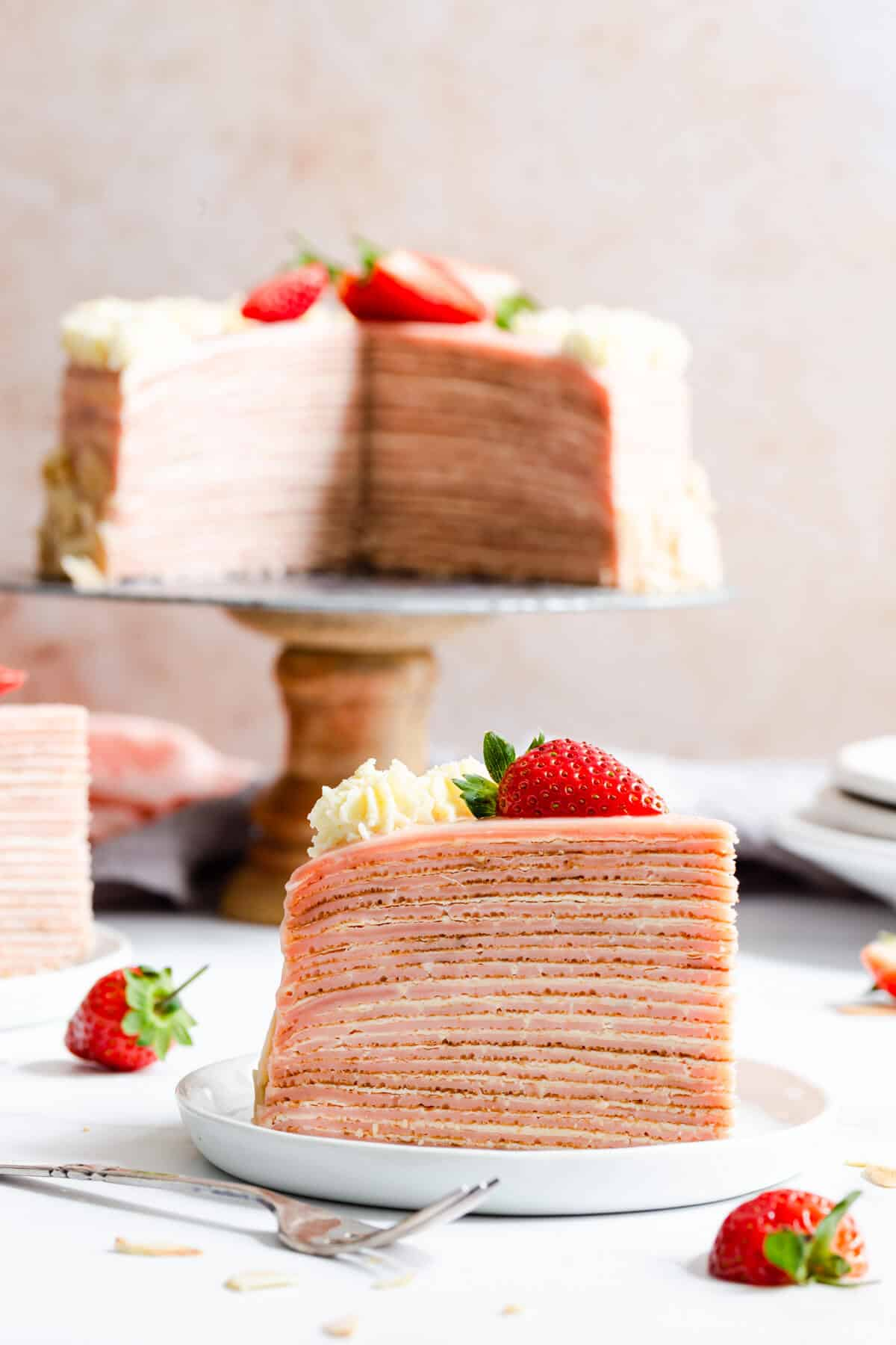 super close up straight ahead angle of a slice of crepe cake with cake in the background