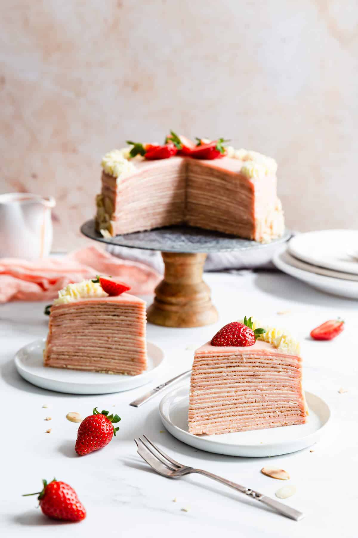 side shot of two individual slices of cake on small plates and cake in the back