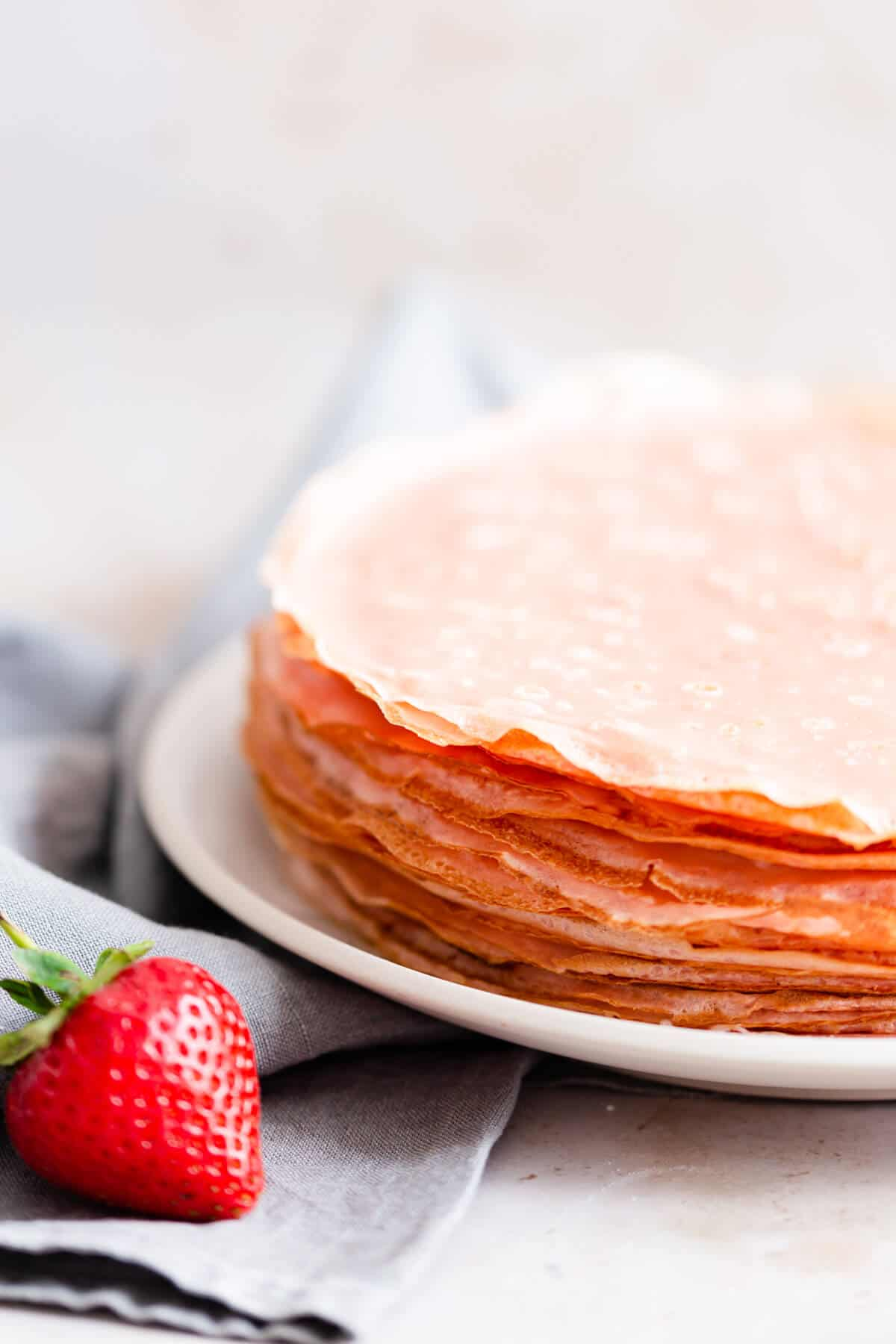 side close up of pink crepes on a plate