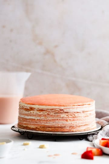 straight ahead shot of naked crepe cake with whipped cream