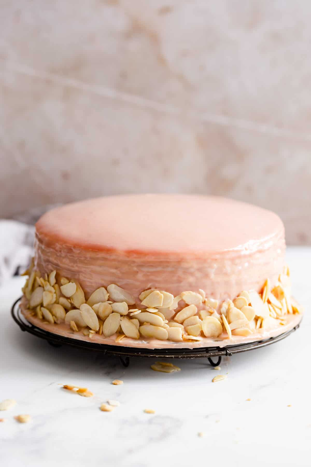 straight ahead angle showing crepe cake covered in strawberry ganache and flaked almonds on sides