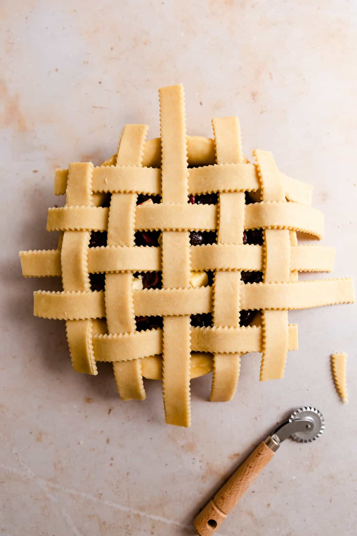 overhead shot of a unbaked pastry lattice on top of the cherry filling