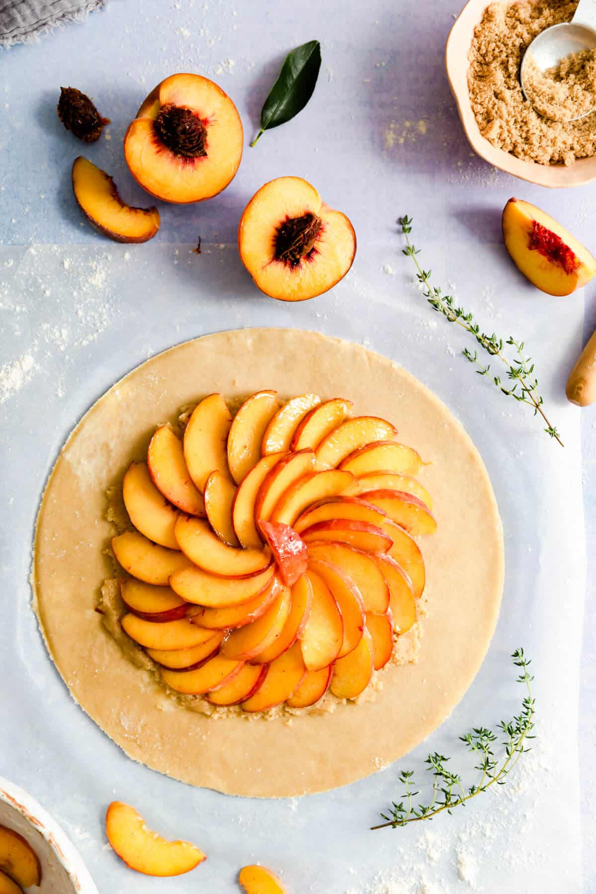 top view of large circle of dough topped with sliced peaches