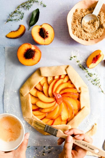 overhead shot of brown sugar peach galette being brushed with egg wash